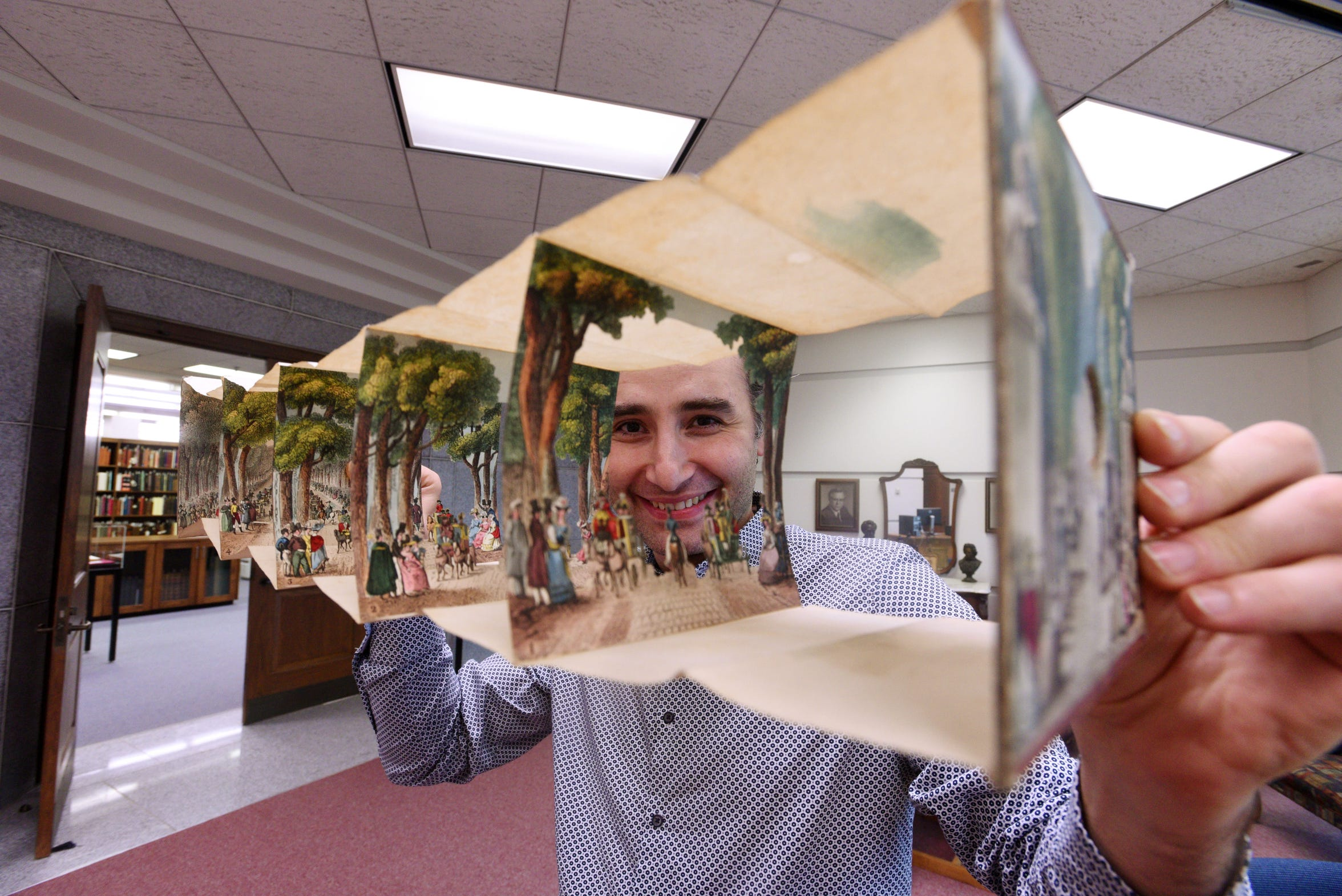 "Alexander Mikaberidze, curator for the rare book collection at Noel Memorial Library, holds ""Optique No. 4, Promenade de Longchamp"", from France dated 1818."