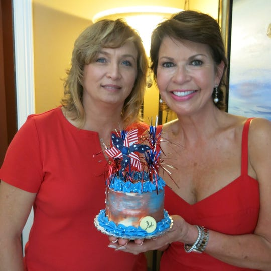 Ellen Ballard and hostess Linda Biernacki show off a confection at the 4th of July party hosted by Biernacki and hubby Richard.