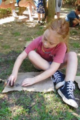 Lydia Ghio works on her charcoal drawing at the Tallahassee Museum's Art Camp.