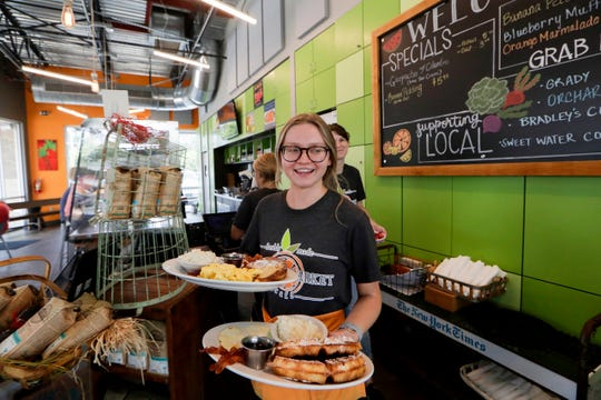 Lea Sisic, a server at Grove Market Cafe, delivers an armload of eggs and waffles to a table during the Sunday brunch rush at the Market Street eatery Sunday, July 7, 2019.