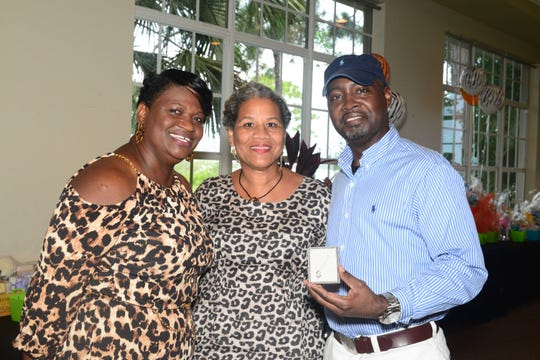 Event Co-chairs Dawn Bloomfield and Lorraine Hunter, left, with raffle prize winner Jay Walker at the Caribbean American Cultural Group's High-Tea, Fashion Show and Silent Auction at the Ballantrae in Port St. Lucie.