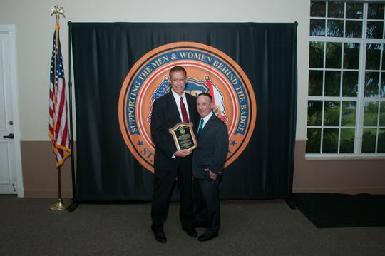 Hundred Club President Jason Berger, right, presents Judge Phil Yacucci with the Friend to First Responder award at the club's 2019 banquet.