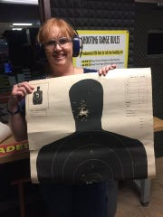 Justina Anuszewski holds up an example of target practice at the gun range.