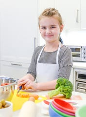 A young girl cuts vegetables in a kitchen.