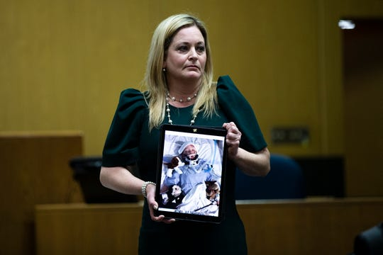 Amy Sytsma holds up a photo of her injured 6-year-old son Tuesday, March 12, 2019, at the Marathon County Courthouse in Wausau, Wis. T'xer Zhon Kha/USA TODAY NETWORK-Wisconsin