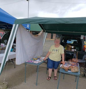 Susan with paintings, copper trees, and books at the Seymour Farmer's Market, July 2, 2019.
