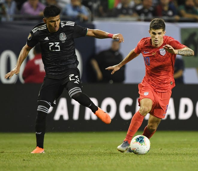 Christian Pulisic chases after the ball with Mexico midfielder Jesus Gallardo.