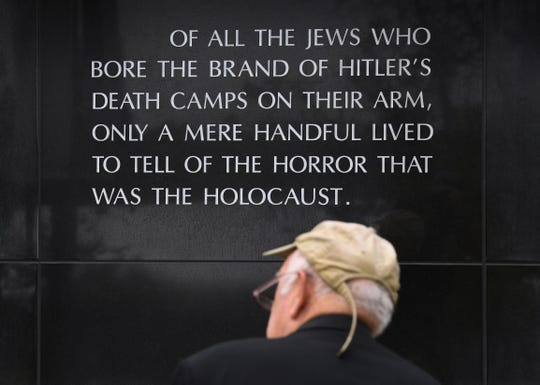 A man sits beside a memorial dedicated to victims of the Nazi terror, during the Yom Hashoah Commemoration event which honors the memories of the victims and survivors of the Holocaust, in Los Angeles on April 28, 2019.