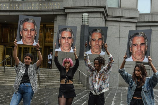 Protesters hold up photos of Jeffrey Epstein outside a courthouse in New York on July 8, 2019.