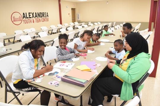 Louise Walls (front left) and Duaa Khawaldeh (front right), two teen counselors at the Alexandria Youth & Teen Center, work with youngsters on arts and craft projects Tuesday, July 9, 2019.