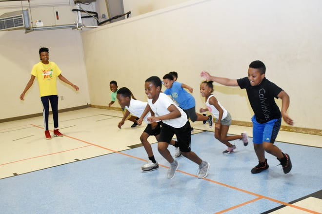 Jaylen Walker (left), a teen counselor at the Alexandria Youth & Teen Center, plays games with youngsters in the center's gym Tuesday, July 9, 2019.