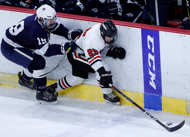 Drew Sutton, right, of Neenah/Hortonville/Menasha battles with Hudson's Kolton Prater during a WIAA state hockey quarterfinal game Feb. 28 in Madison.