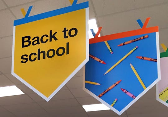 """In this 2018 file photo, """"back to school"""" signage hangs in a store in Methuen, Mass. It might seem like you've been saving for back to school since you packed your children's backpacks last fall. But after replacing worn-out erasers, outgrown clothes and an outdated laptop, you may still feel the financial pinch."""