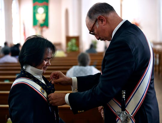 Richard Chengson, the assembly commander for the Knights of Columbus, assist Angel Nhan with his tie Saturday at Sacred Heart Catholic Church.