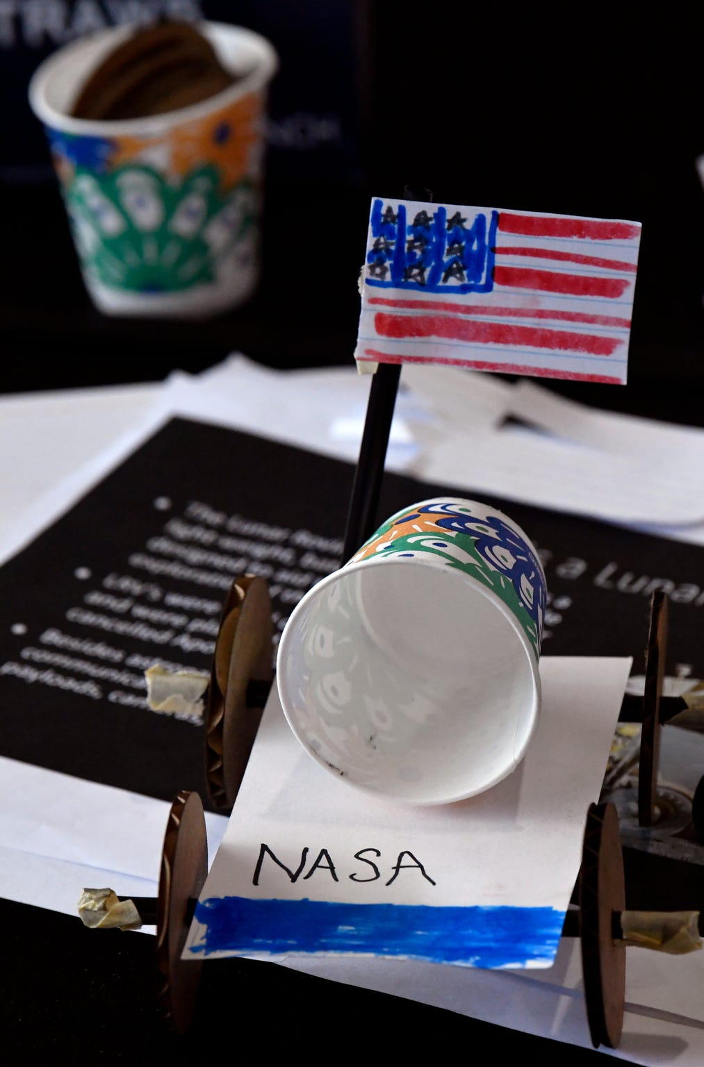A finished child's craft project depicting a rover sits on a table near the Saturn V rocket at the Johnson Space Center. Space Center Houston runs trams to the park, as well as to other locations at JSC throughout the day