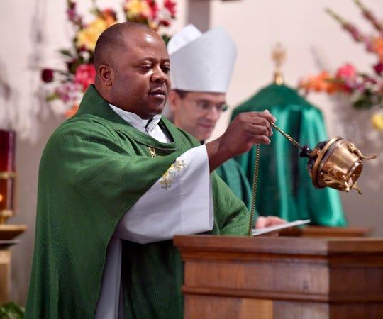The Rev. Albert Ezeanya blesses his pulpit using incense as Bishop Michael Sis reads a prayer behind him Saturday.