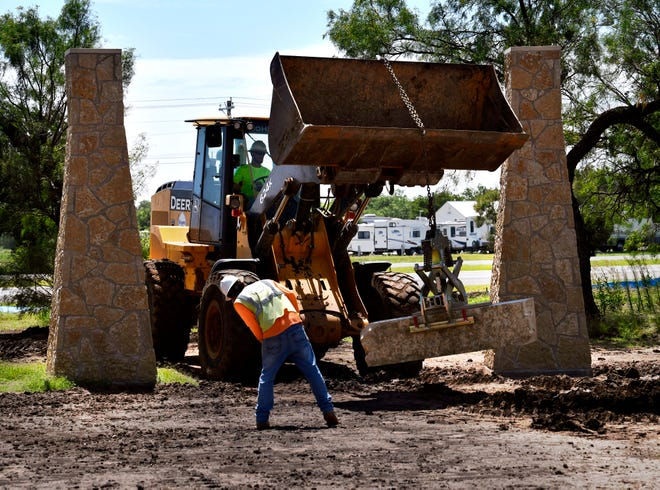 Workmen bring in stone blocks as construction at Dyess Memorial Park continues Tuesday.