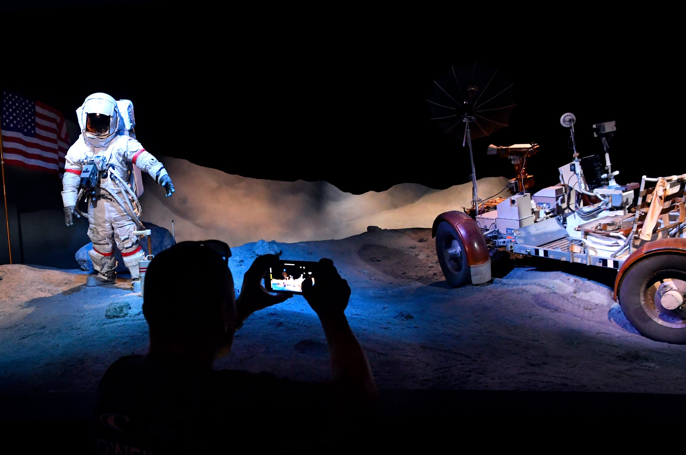 A visitor to Space Center Houston's Starship Gallery photographs the LG-1 Lunar Roving Vehicle trainer on exhibit .