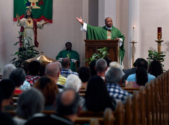 Father Albert Ezeanya addresses the congregation after being installed as the new priest at Sacred Heart Catholic Church on Saturday.