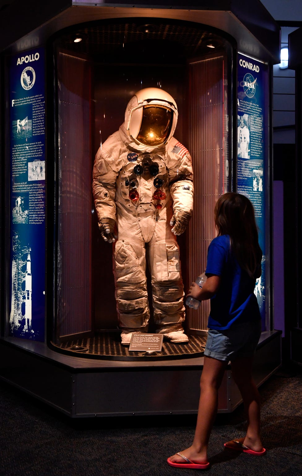 "Eisley Jones, 8, of Seabrook studies the spacesuit worn on the moon by Astronaut Charles ""Pete"" Conrad during Apollo 12 in 1969. On exhibit in the Space Center Houston Astronaut Gallery, It is one of two Lunar suits on display outside of the Smithsonian Air and Space Museum. Eisley was visiting the museum with her father Tyler and brother Atticus."