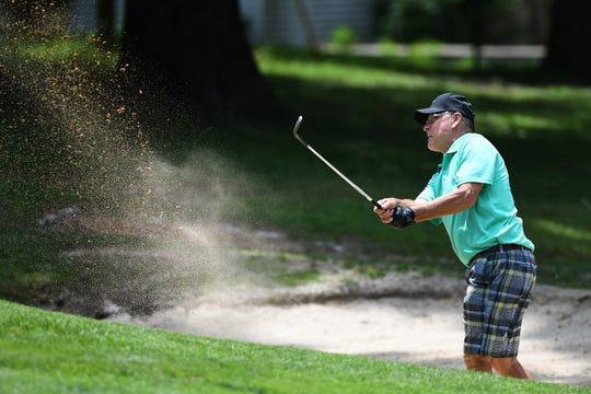 Gary Johnson, of Asheville, hits his ball out of a sand trap during the first day of the 60th annual Skyview Golf Tournament at the Asheville Golf Course on July 9, 2019.