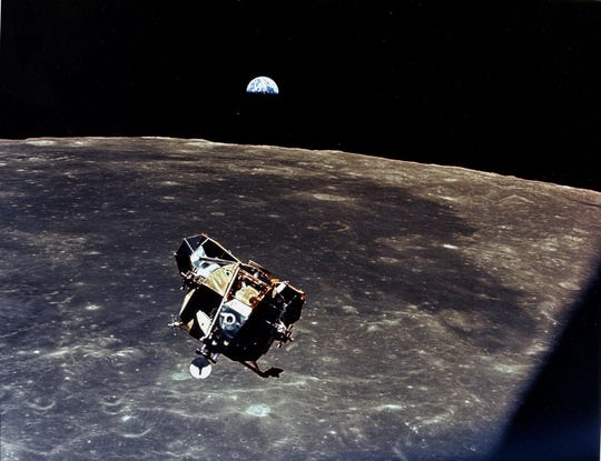 With Earth in the background, the Lunar Module ascent stage with Neil Armstrong and Buzz Aldrin approaches a rendezvous with the Apollo Command Module.