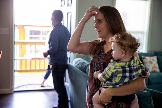 Cortny Robertson holds her son, Caleb Robertson, 7 months, and enters their new home on Tuesday, July 9, 2019. The family of eight had been living in a tiny home after an extension of their home was damaged during Hurricane Harvey. It was rebuilt with the help of several agencies.