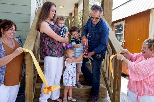 The Robertson family, Cortny (clockwise from center left), Caleb, 7 months, Logan, 5, Curtis and Madison cut the ribbon before receiving the key to their new home on Tuesday, July 9, 2019. The family of eight had been living in a tiny home (to the right) after an extension of their home was damaged during Hurricane Harvey. It was rebuilt with the help of several agencies.