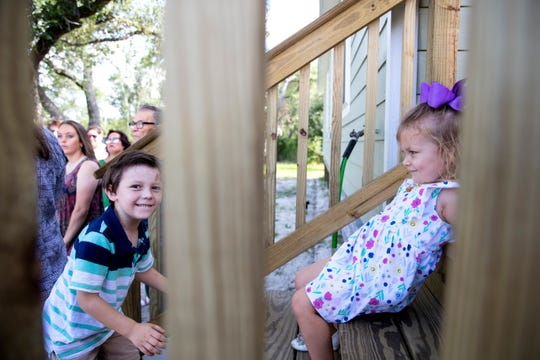 Siblings Logan, left, 5, and Madison, 3, Robertson, play during a ceremony in which the family of eight receives the keys to their new home on Tuesday, July 9, 2019. The family has been living in a tiny home after an extension of their home was damaged during Hurricane Harvey. It was rebuilt with the help of several agencies.