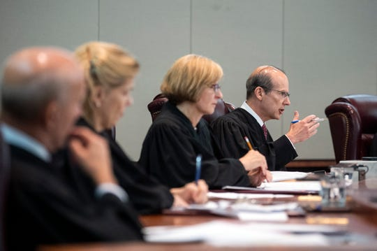 Chief Justice Stuart Rabner, right, addresses defense attorney Amelia Carolla as a disciplinary hearing before the New Jersey Supreme Court is held Tuesday, July 9, 2019 in Trenton, N.J.