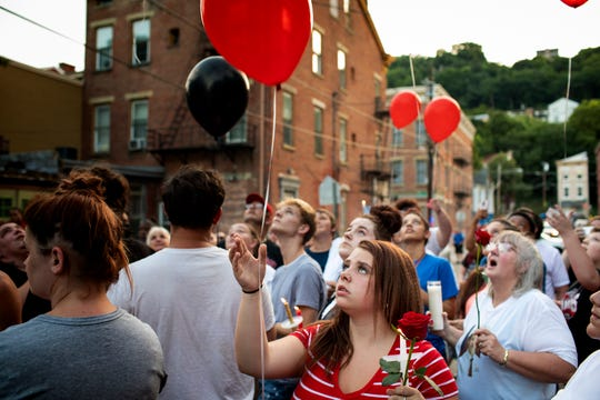 McKenzie Hansel releases a balloon at a candlelight vigil for her brother, Cameron Franklin, who was shot and killed on Saturday on Storrs Street in Lower Price Hill Monday, July 8, 2019.
