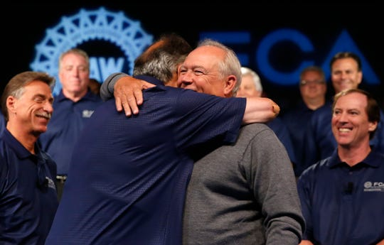 The late Fiat Chrysler Automobiles CEO Sergio Marchionne, left, and then United Auto Workers President Dennis Williams squeezed during a ceremony to mark the opening of the contract negotiations in 2015.