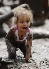 Oak Park resident Alexandria King, 2, plays in the mud during Mud Day at Edward Hines Park in Westland on Tuesday, July 9, 2019.