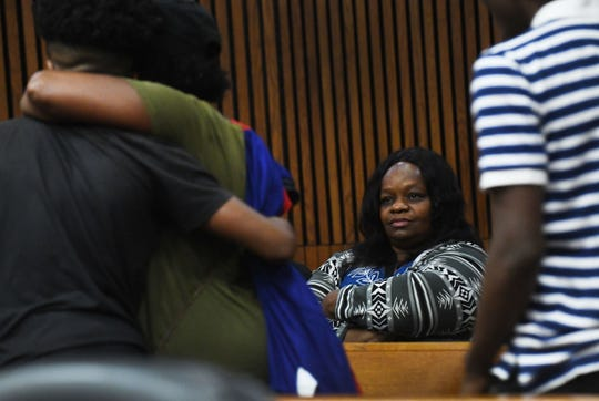 Murdered teen Je'Rean Blake's mother Lyvonne Cargill looks on as the defendants family members embrace and leave the courtroom after the hearing.