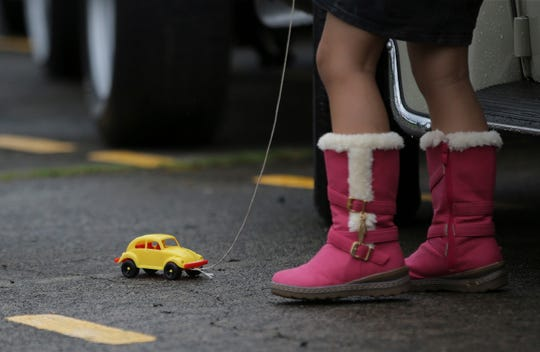 In this June 22, 2014, file photo a Filipino girl plays with a toy Volkswagen Beetle as she joins activities to celebrate World Volkswagen Day at Camp Aguinaldo in suburban Quezon city, north of Manila, Philippines.
