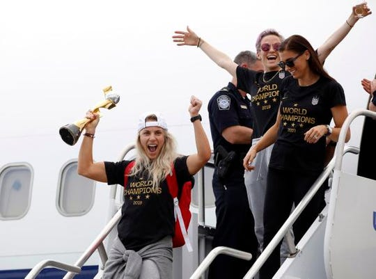 Members of the United States women's soccer team, winners of a fourth Women's World Cup, including Julie Ertz, left, Megan Rapinoe, top center, and Alex Morgan, top right, celebrate after arriving at Newark Liberty International Airport in Newark, New Jersey.