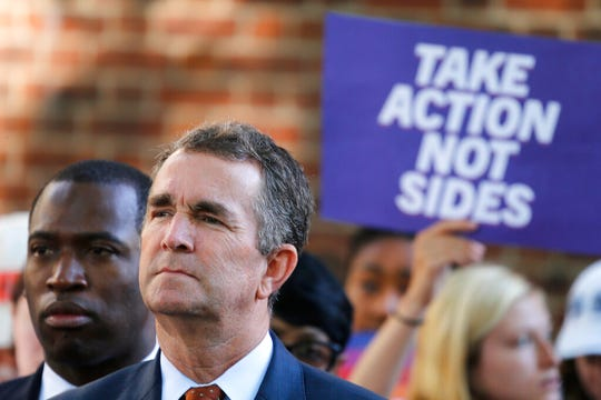 Virginia Gov. Ralph Northam, right, listens to speakers along with Richmond Mayor Levar Stoney, left, during a rally at the State Capitol in Richmond, Va., Tuesday, July 9, 2019. Governor Northam called a special session of the General Assembly to consider gun legislation in light of the Virginia Beach Shootings.