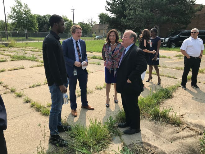 Dakkota Integrated Systems CEO Andra Rush, center, listens as Detroit Mayor Mike Duggan talks to 23-year-old Branden Horner, who came to the announcement of a $55-million manufacturing facility Tuesday hoping to apply for a job.