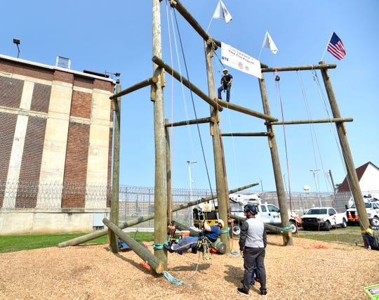 Students inmates demonstrate their skills on poles in front of Block 10 at the Parnell Vocational Village, Tuesday morning, July 9, 2019.