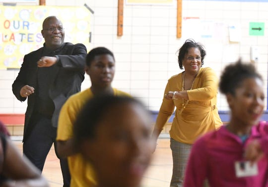 Flint Community Schools Superintendent Derrick Lopez and school board President Diana Wright dance with students during a gym class.