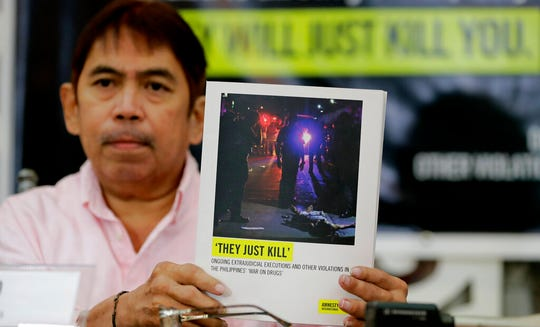 Butch Olano, Amnesty International Section Director in the Philippines, holds a copy of the Amnesty's report during a news conference, Monday, July 8, 2019, in Manila, Philippines. Amnesty International has urgently called for international pressure and an immediate U.N. investigation to help end what it says are possible crimes against humanity in the Philippine president's bloody anti-drug crackdown.