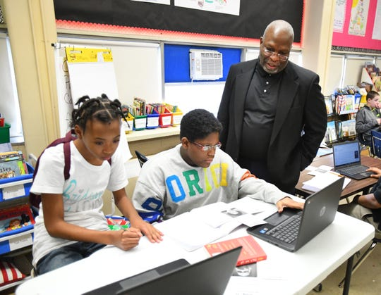 Flint Community Schools superintendent Derrick Lopez looks on as Tyra Rimmer, 10, and Zyrianaa Johsnon, 10, participate in a social studies lesson utilizing school computers at Freeman Elementary School in Flint.