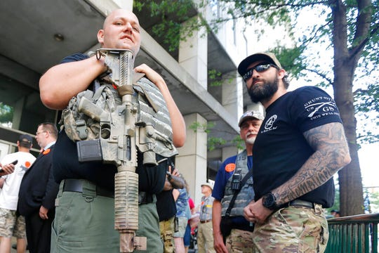 Gun rights supporters hold weapons outside the Capitol office building at the State Capitol in Richmond, Va., Tuesday, July 9, 2019.