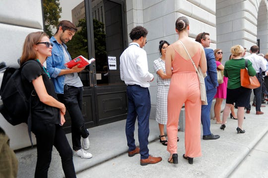 People wait in line to enter the 5th Circuit Court of Appeals to sit in overflow rooms to hear arguments in New Orleans, Tuesday, July 9, 2019. The appeals court will hear arguments today on whether Congress effectively invalidated former President Barack Obama's entire signature health care law when it zeroed out the tax imposed on those who chose not to buy insurance. A Texas judge in December ruled it was invalid, setting off an appeal by states who support the law.