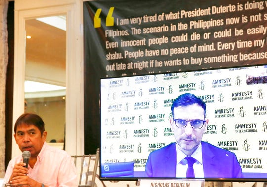 Butch Olano, Amnesty International Section Director in the Philippines, left, and Nicholas Bequelin, Regional Director for East and Southeast Asia, (on screen) answer questions from the media during a tele-news conference Monday, July 8, 2019, in Manila, Philippines.