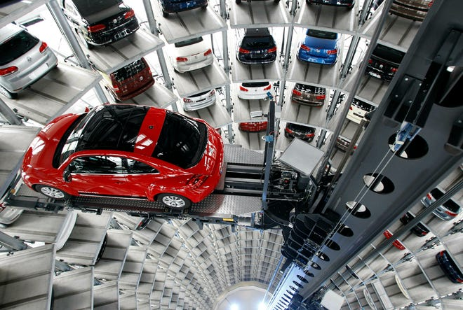In this March 12, 2012, file photo a Volkswagen New Beetle car is lifted inside a delivery tower after the company's annual press conference in Wolfsburg, Germany.
