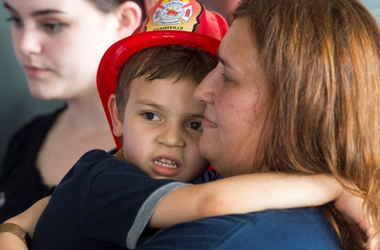 Leo Hassebrock, left, hugs his mother Dianna Hassebrock, left, during a press conference at EFD Fire Station #1 Tuesday, July 9, 2019. Hassebrock was rescued after falling nearly 30 feet down a pipe on July 4, 2019.