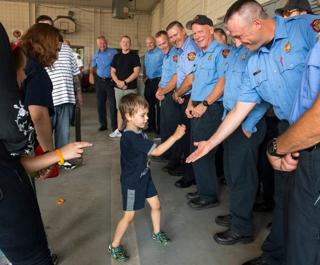 Leo Hassebrock, center, gives Evansville Firefighter Brett DeVault, right, a high five during a press conference at EFD Fire Station #1 Tuesday, July 9, 2019. Hassebrock was rescued after falling nearly 30 feet down a pipe on July 4, 2019.