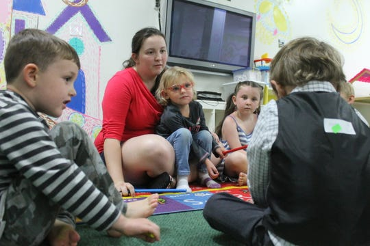 Taia Selburg leads a game at Funshine Early Learning Center and Drop-In Child Care Tuesday, July 9, 2019 as Jane Strong sits in her lap. Selburg teaches at the center, which announced it would close Sept. 14, 2019.