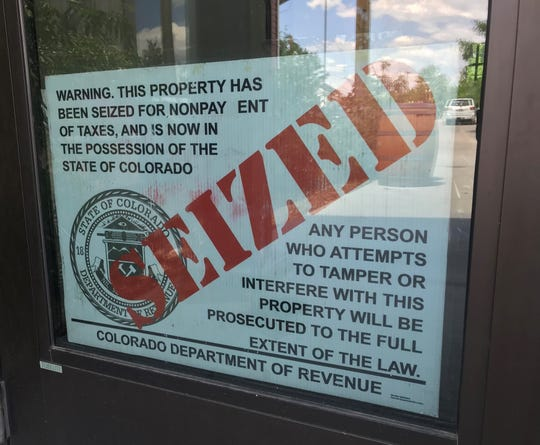 A seized sign is attached to the door of Peloton Cycles on Tuesday after tax compliant agents shut down the business.